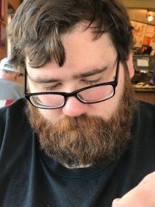 Photo of Matthew Marvin Distler [heavy set, bearded white male with brown hair and black rimmed eyeglasses]